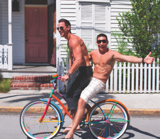 Two shirtless, muscled men on bikes in Key West, Florida.