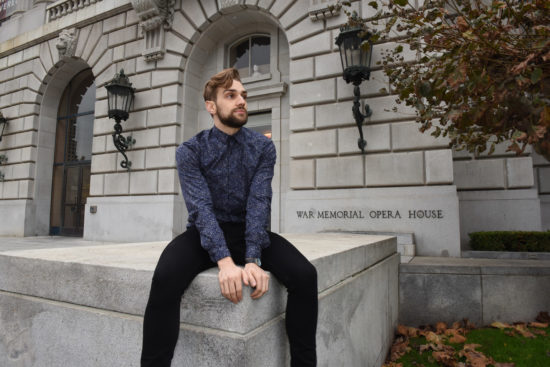 Myles Thatcher poses in a blue sweater in front of the War Memorial Opera House in San Francisco.