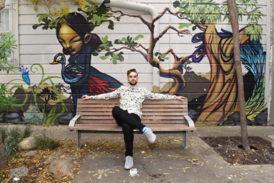 Myles Thatcher poses in a colorful top while sitting on a bench across from Blue Bottle coffee in Hayes Valley, San Francisco. There is a beautiful mural in the background.