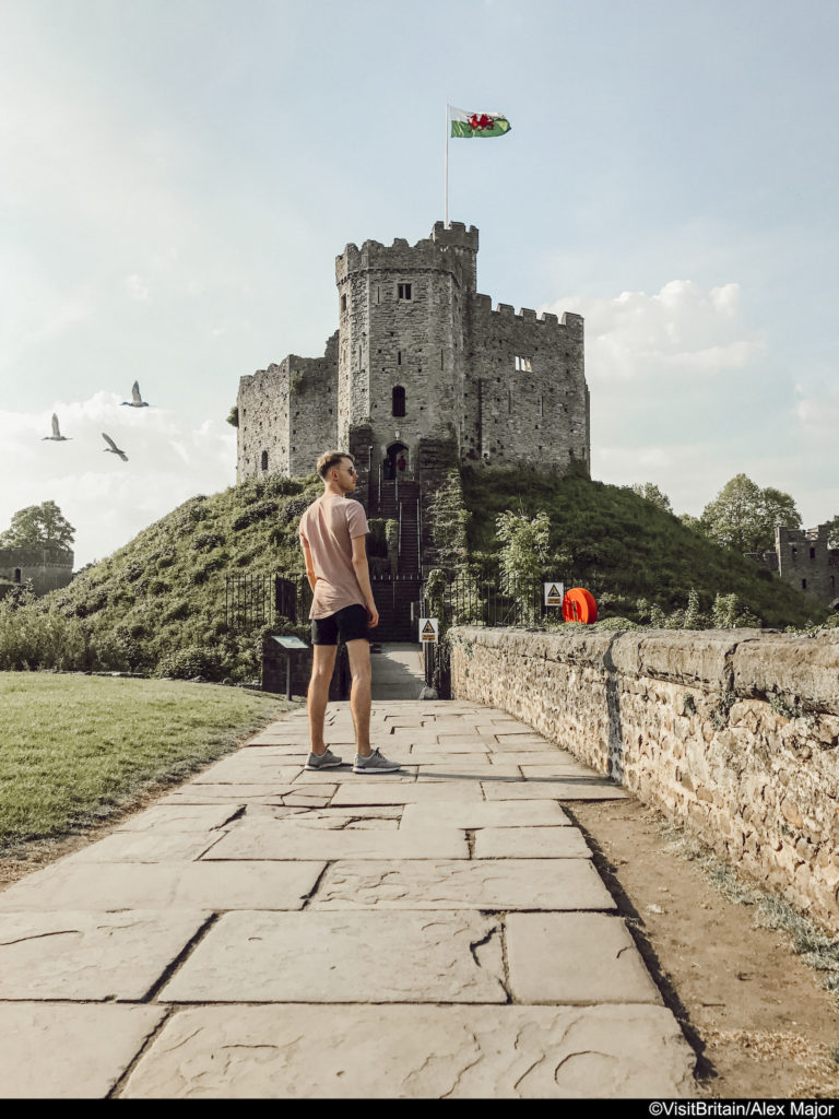 A gay man poses in front of Cardiff castle in Wales