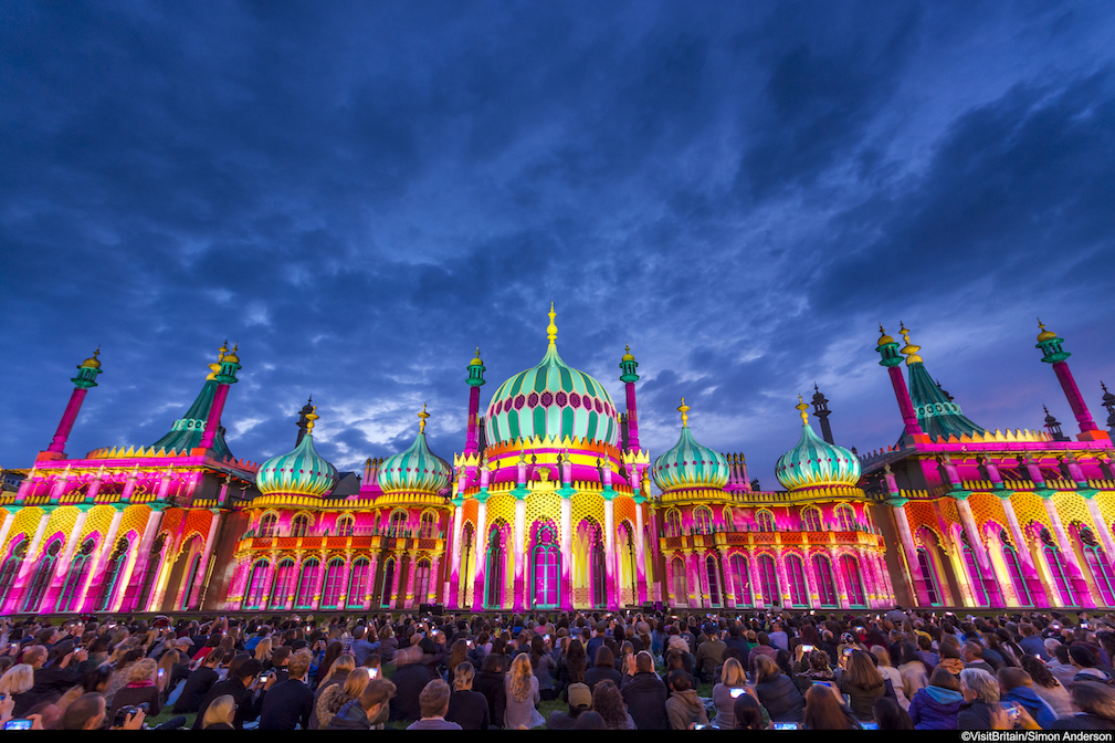 Crowd of people in front of the Royal Pavilion at dusk, lit up in a range of vivid colours, pink, green, yellow and purple, Brighton, East Sussex, England.