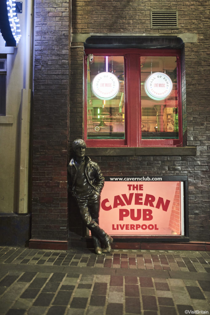 A wax sculpture of John Lennon rests against a red sign for Cavern Pub, in Liverpool UK