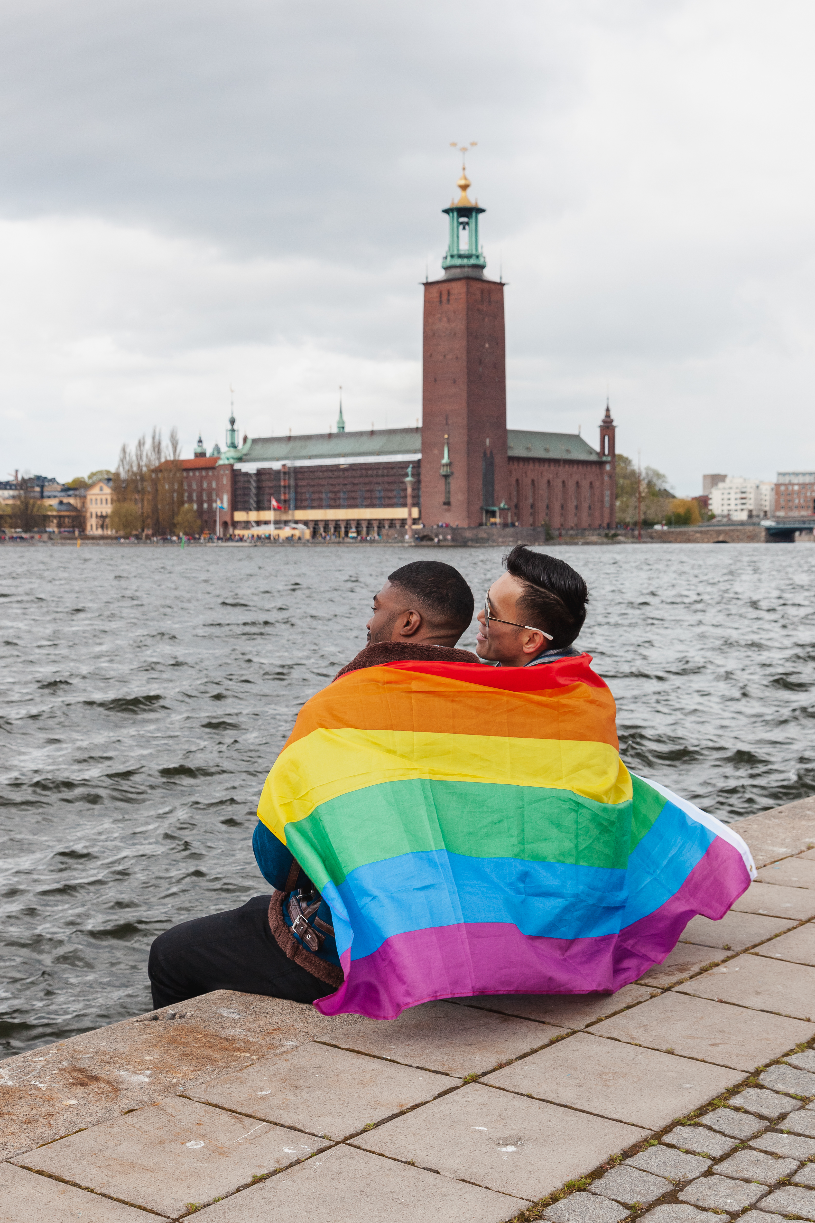 Two gay men sit on the water in Stockholm with a rainbow flag wrapped around them both.