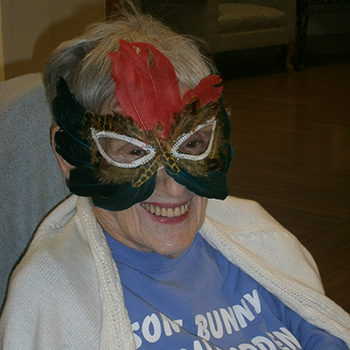 female resident with feathered mardi gras mask