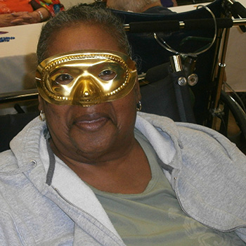 female resident with gold mardi gras mask