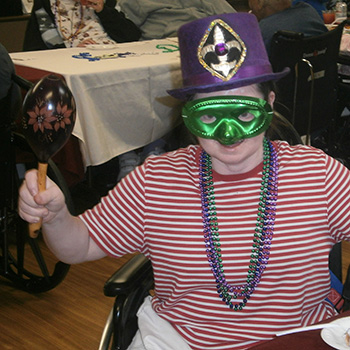 resident with mardi gras hat, mask, and beads