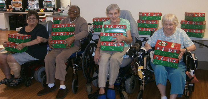residents with wrapped gifts for operation christmas child