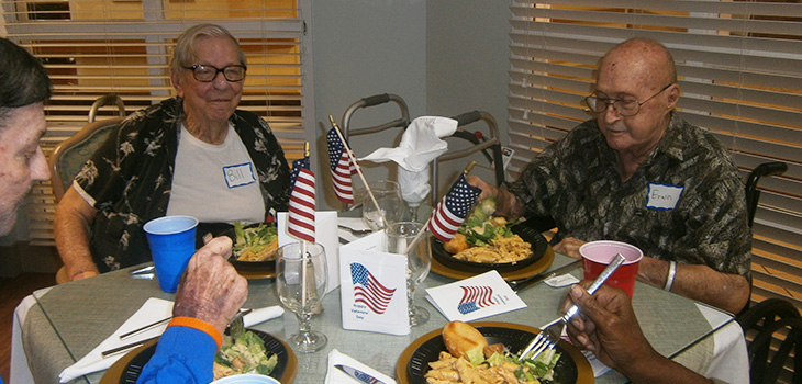 residents at table with flags