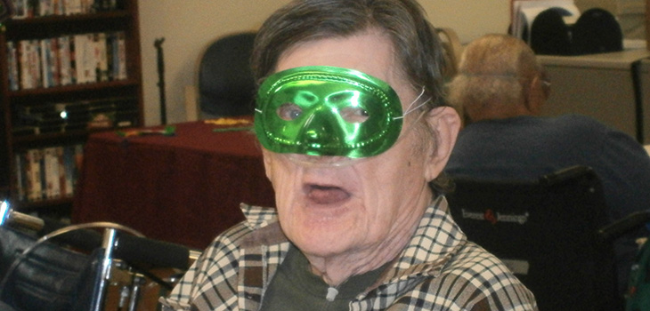 resident with green mardi gras mask