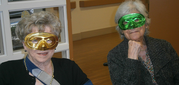 female residents with green and gold mardi gras masks