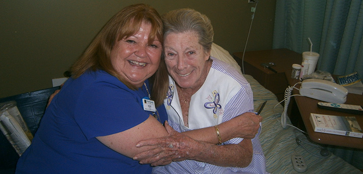 staff member embracing smiling resident