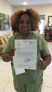 Belinda holding her letter of recognition from Senator Steube