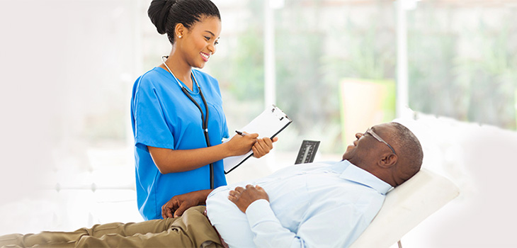 Nurse with a clip board smiling while staring at a man in a bed