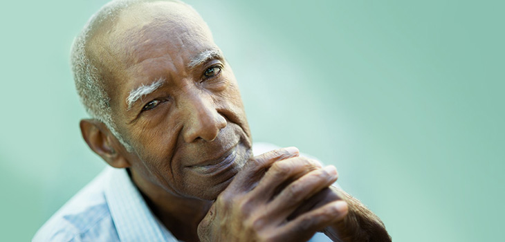 African American elderly man with his hands folded by his chin