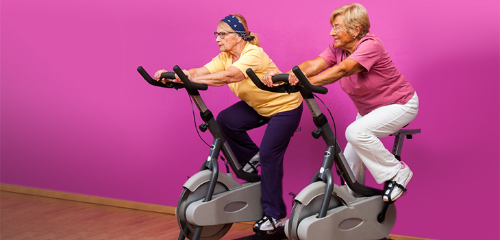 two woman on exercise bikes