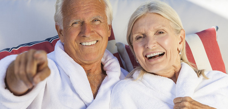 couple sitting together with bath robes on and colorful pillows behind them