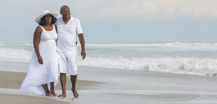 couple walking arm in arm by the sea shore barefoot with the waves crashing beside them