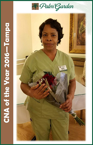 CNA of the year 2016 Denise Nichols in scrubs holding flowers
