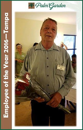 Employee of the Year John Irvine holding flowers