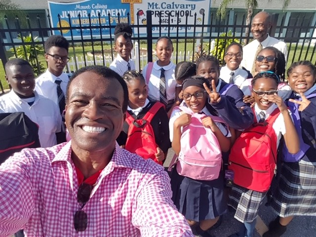 Pastor Brown smiling in front of a group of children holding up their back to school items!