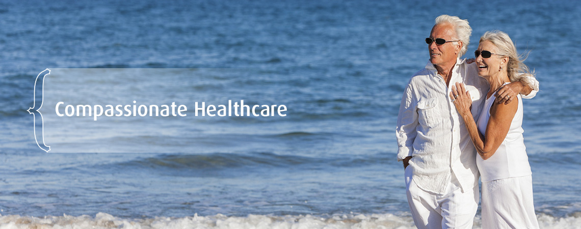 couple dressed in white embracing on the beach – Compassionate healthcare