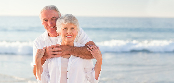couple on the beach, he has his arms around her