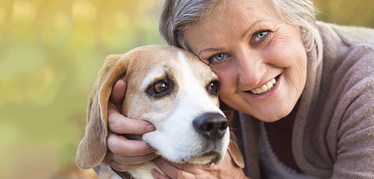 smiling woman with pretty blue eyes hugging a dog