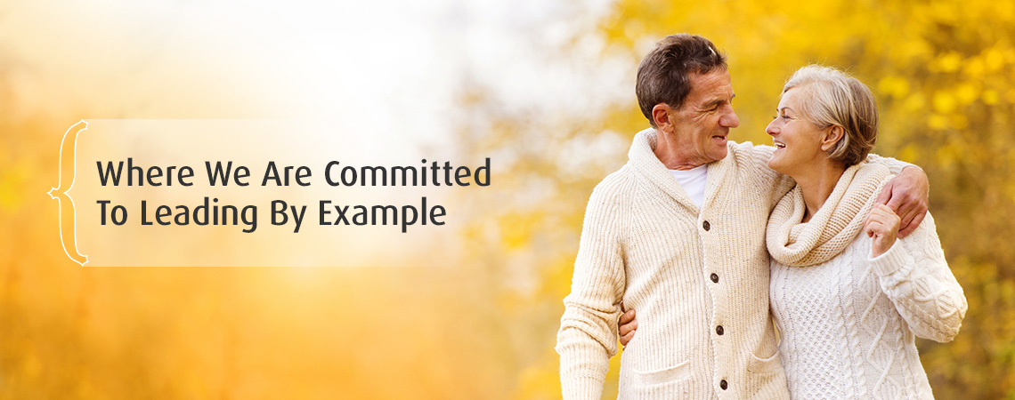 couple walking in fall – where we are committed to leading by example