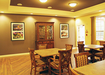 small dining area with 4 seat tables and artwork on the walls