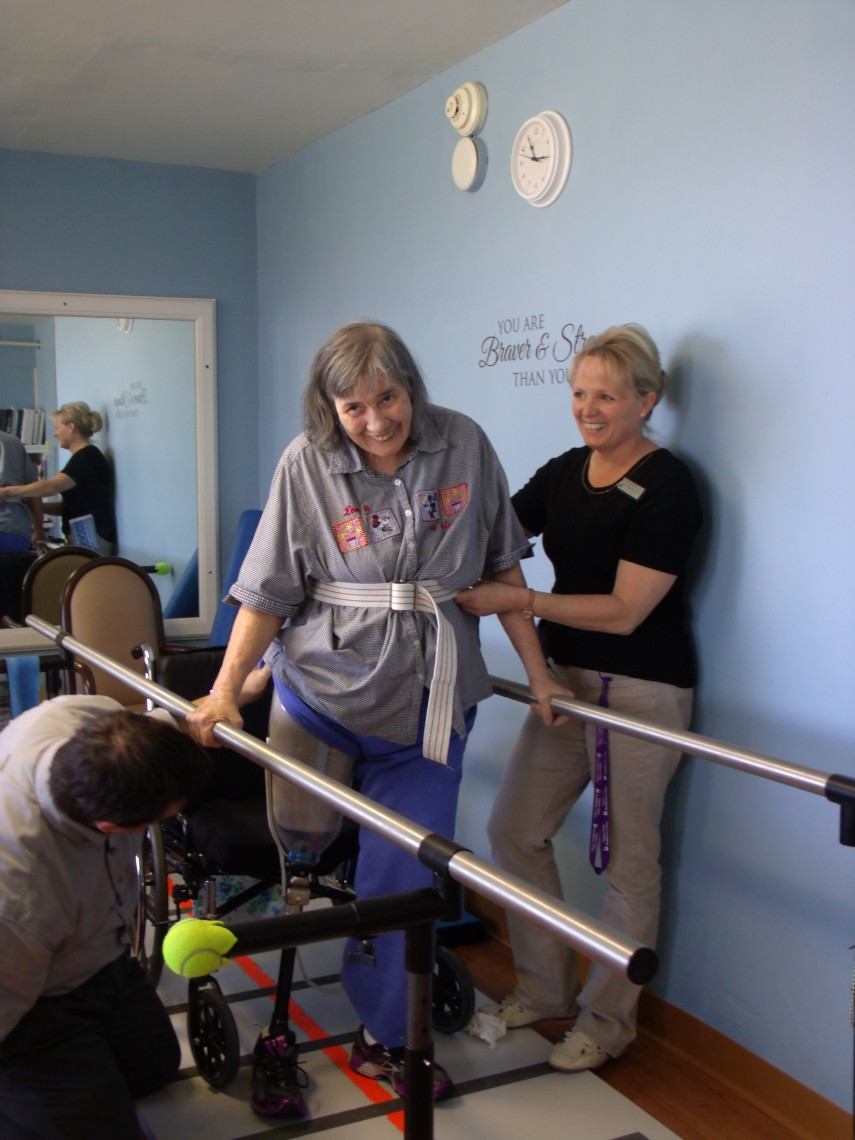 A patient walking with rehab staff on the parallel bars