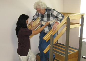 A woman walking down the stairs with the help of rehab staff