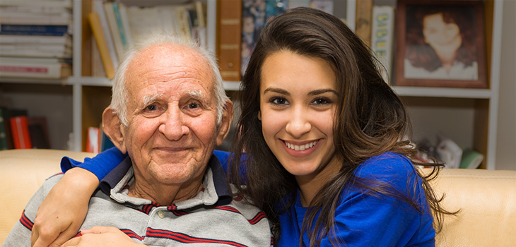 A grandfather and granddaughter smiling together