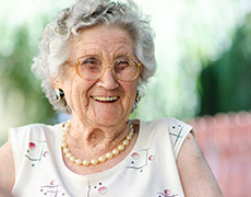 smiling elderly woman wearing pearls and glasses