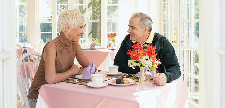 couple enjoying a meal inside in a sunlit dining room