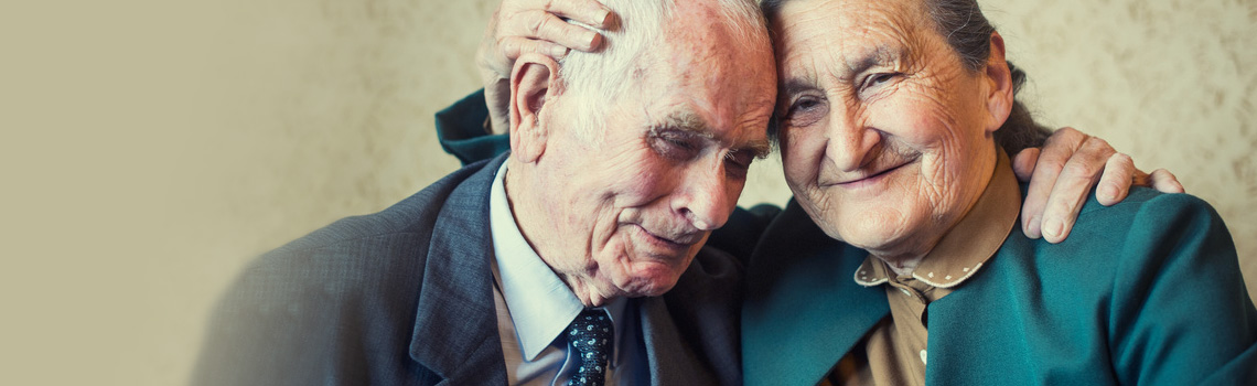 elderly couple with their heads tilted together
