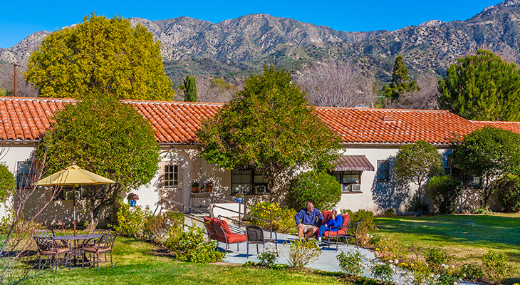 Couple seated outside Assisted Living on a beautiful sunny day with the mountains in the background