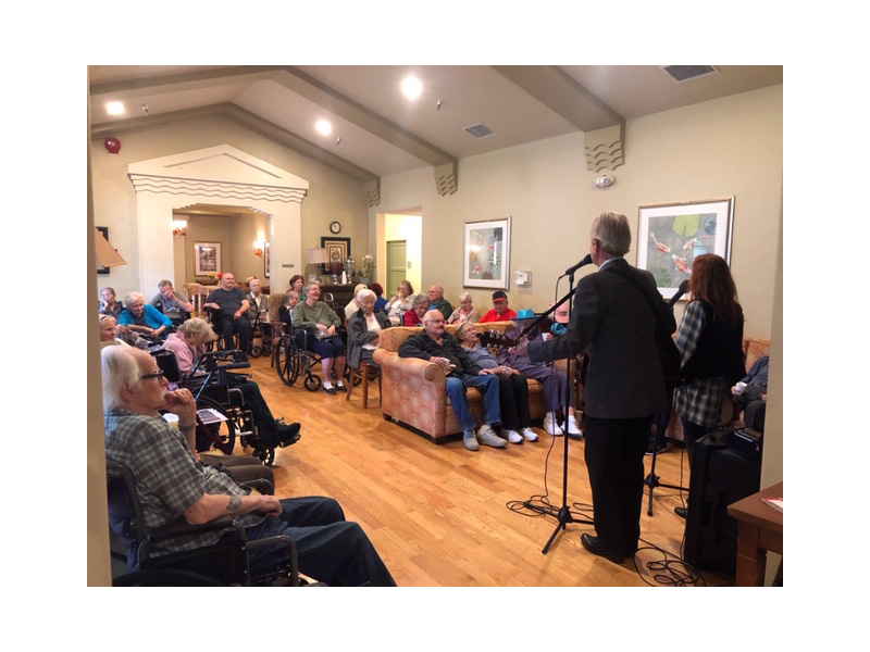 Musicians performing to a packed house full of residents enjoying the concert
