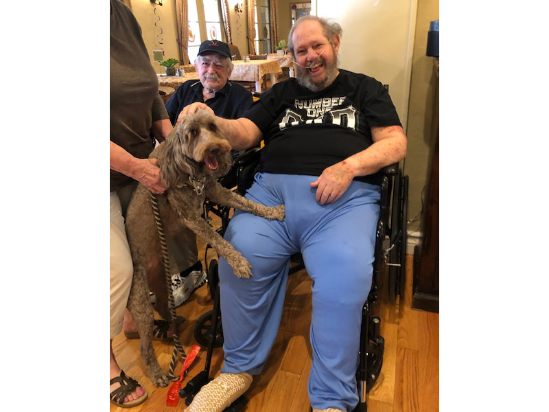 A therapy dog visits with residents