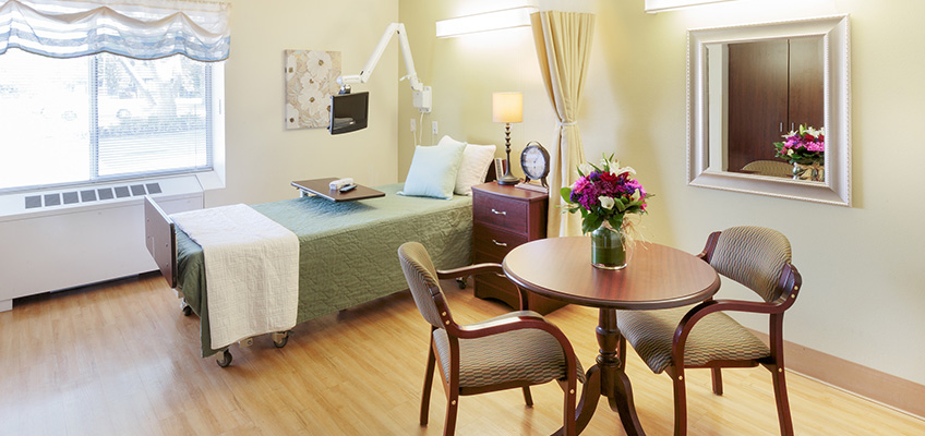 resident room with bed and bistro table
