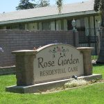 Rose Garden Residential Care sign surrounded by grass