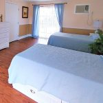 Double occupancy bedroom with nicely made beds, clean hardwood floors and a large window letting in the sunlight.