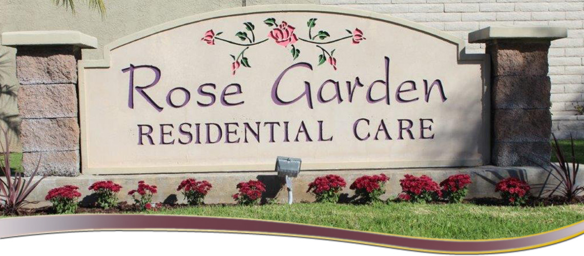Rose Garden Residential Care sign out front with flowers along the base of the sign.