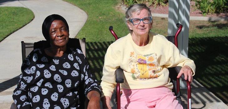 Two residents sitting outside together enjoying the sunshine.