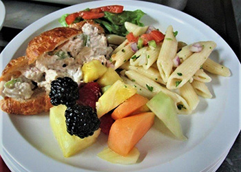 Tuna salad on a croissant with fruit salad and pasta salad on the side.