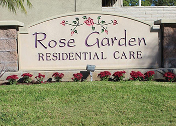 Rose Garden Residential Care sign with flowers along the front and lush grass.