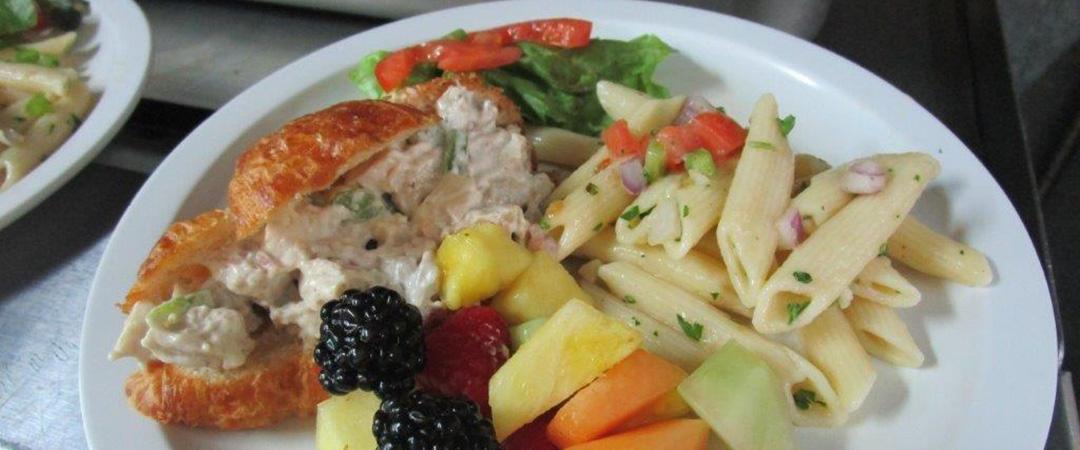 A sandwich, fresh fruit, and pasta salad.