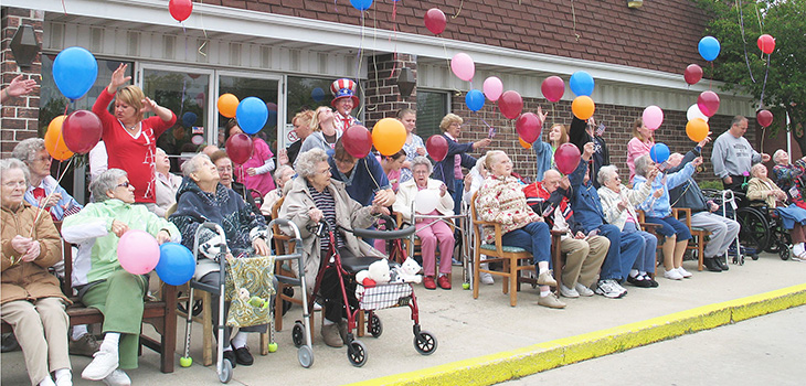 residents sitting together outside with balloons