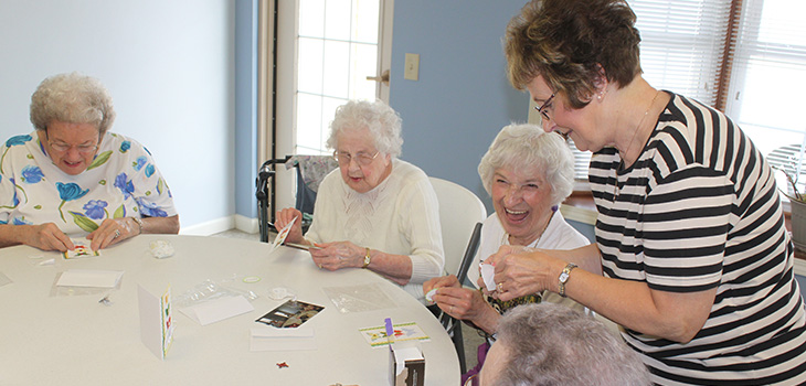 pleasant hill residents playing bingo together with the help of an employee