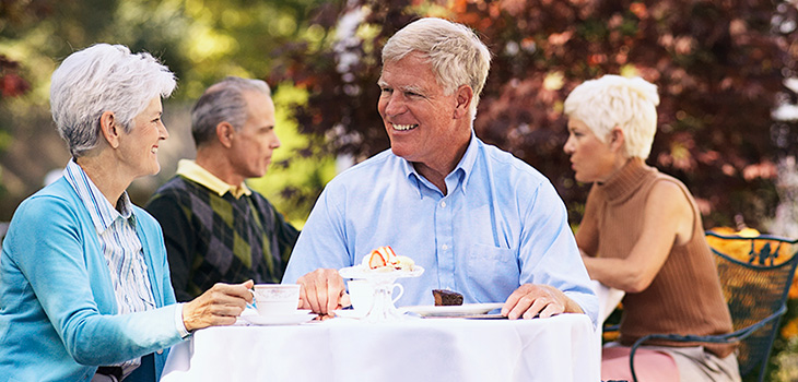 residents sitting together drinking coffee and eating cake