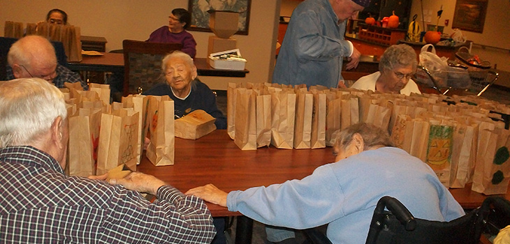 Residents smiling around a table filled with brown bags filled with goodies
